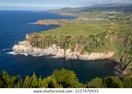 View of rocky nothern coast of Sao Miguel Island, Azores, Portugal seen from the Miradouro de Santa Iria scenic viewpoint. An enchanting and tranquil scene of lush green foliage and Atlantic ocean