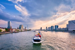 View of Rotterdam cityscape and Erasmus bridge over Nieuwe Maas with cargo ships and boats. Rotterdam, Netherlands