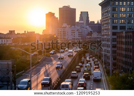 View of rush hour traffic on the Brooklyn Queens Expressway in New York City with sunset light in background