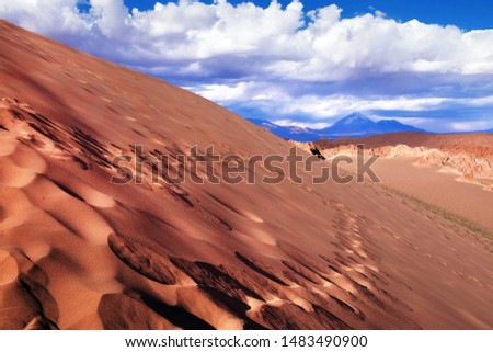 View of sand dunes and rocky hills in the Mars Valley near San Pedro de Atacama against a blue dramatic sky above volcanoes. #1483490900
