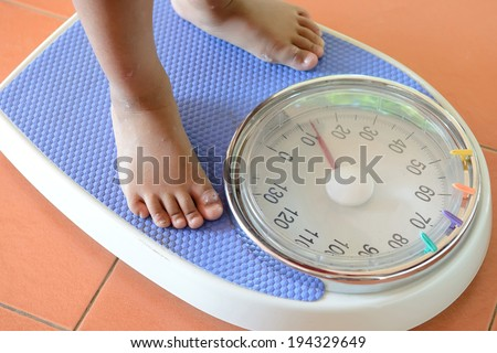 view of scales on a floor and kids feet