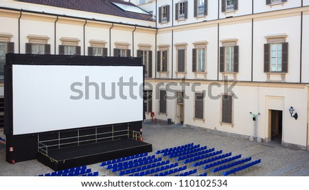 View of screen and Empty blue chairs for outdoor cinema