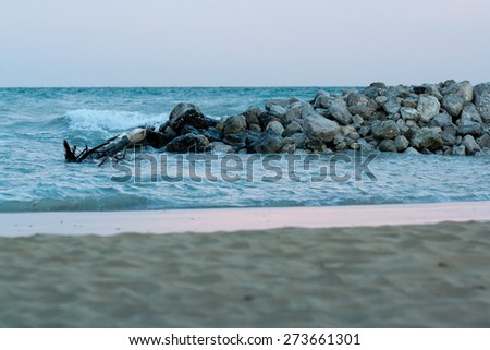 view of sea and sand beach with stones at sunset in the evening, sea tide, natural photo, Bibione, Italy