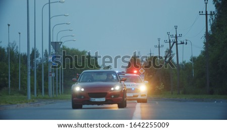 View of self-willed young man driving on modern sports car from the police. Police officer cop chasing a thief driving a patrol car on the highway at daytime. Police in pursuit. Foto stock ©