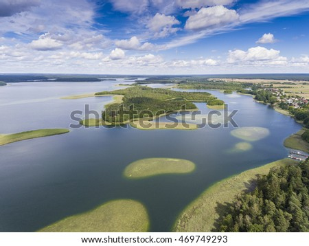 View of small islands on the lake in Masuria and Podlasie district, Poland. Blue water and whites clouds. Summer time. View from above. #469749293