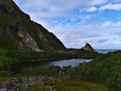 View of small lake Solsvatnet located at the coast of the Norwegian Sea near village Bleik, Andøya island, Vesterålen, Norway surrounded by dense vegetation and rugged mountains on cloudy summer day.