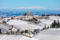 View of small medieval town and vineyards on the hills covered in snow in Piedmont, Northern Italy.