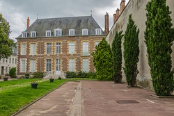 View of small public garden and courtyard of XV century Groslot building - formerly residence of local magistrate. Groslot building then used as Town Hall during French Revolution. Orleans, France.