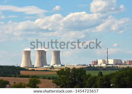 View of smoking chimneys of nuclear power plant, power lines and forest, under blue sky with white clouds