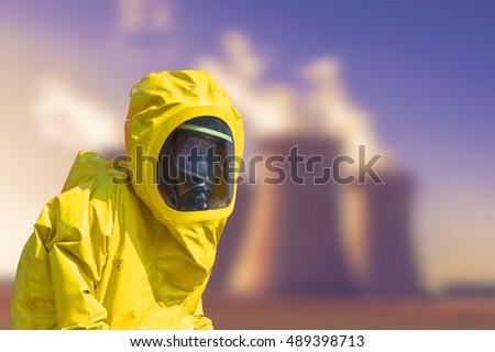 View of smoking coal power plant and men in protective hazmat suit