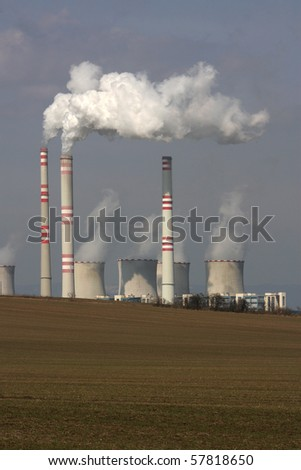 view of smoking power plant over the field