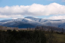 View of snow covered Appalachian Mountains under a blue sky in Virginia.