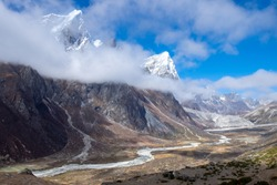 View of snow top peaks and cloudy blue sky with snow melt creek in a mountain valley, between Dingboche and Louche, Everest base camp trekking trail, EBC, Sagarmatha National Park, Nepal