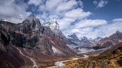 View of snow top peaks and cloudy blue sky with snow melt creek in a mountain valley, between Dingboche and Lobuche, Everest base camp trekking trail, EBC, Sagarmatha National Park, Nepal
