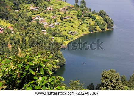 View of some homesteads among orchards on the shore of the 4.43 km2-784 ms.high Phewa tal-lake seen from the way down Ananda Hill and opposite Pokhara city. Kaski district-Gandaki zone-Nepal.