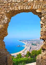 View of Spanish beach through a stone door of the St. John Castle of resort town Blanes in summertime. Costa Brava, Catalonia, Spain
