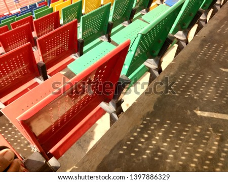 View of stadium with empty seat. Colorful seat in soccer stadium when holiday. Blue, green, red and yellow iron seats. Landscape of free arena seating.   #1397886329