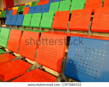 View of stadium with empty seat. Colorful seat in soccer stadium when holiday. Blue, green, red and yellow iron seats. Landscape of free arena seating.   #1397886332