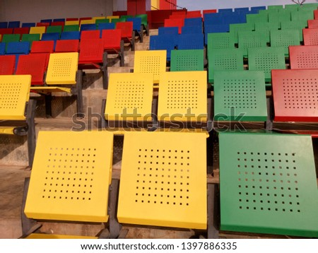 View of stadium with empty seat. Colorful seat in soccer stadium when holiday. Blue, green, red and yellow iron seats. Landscape of free arena seating.   #1397886335