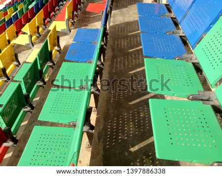 View of stadium with empty seat. Colorful seat in soccer stadium when holiday. Blue, green, red and yellow iron seats. Landscape of free arena seating.   #1397886338