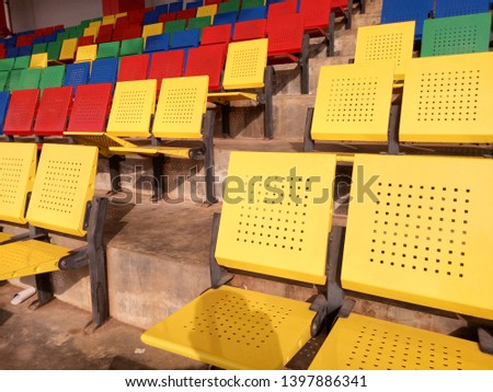 View of stadium with empty seat. Colorful seat in soccer stadium when holiday. Blue, green, red and yellow iron seats. Landscape of free arena seating.   #1397886341