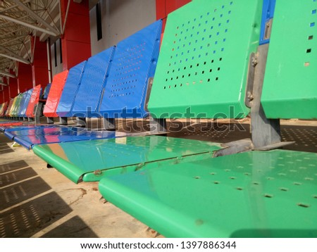 View of stadium with empty seat. Colorful seat in soccer stadium when holiday. Blue, green, red and yellow iron seats. Landscape of free arena seating.   #1397886344