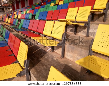 View of stadium with empty seat. Colorful seat in soccer stadium when holiday. Blue, green, red and yellow iron seats. Landscape of free arena seating.   #1397886353