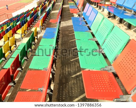 View of stadium with empty seat. Colorful seat in soccer stadium when holiday. Blue, green, red and yellow iron seats. Landscape of free arena seating.   #1397886356