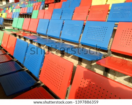 View of stadium with empty seat. Colorful seat in soccer stadium when holiday. Blue, green, red and yellow iron seats. Landscape of free arena seating.   #1397886359