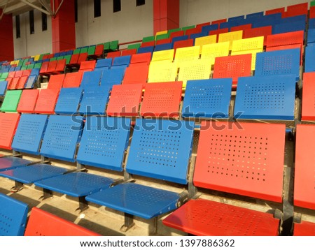 View of stadium with empty seat. Colorful seat in soccer stadium when holiday. Blue, green, red and yellow iron seats. Landscape of free arena seating.   #1397886362