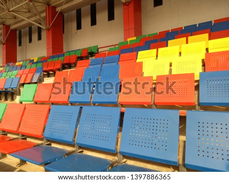 View of stadium with empty seat. Colorful seat in soccer stadium when holiday. Blue, green, red and yellow iron seats. Landscape of free arena seating.   #1397886365