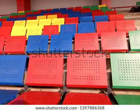View of stadium with empty seat. Colorful seat in soccer stadium when holiday. Blue, green, red and yellow iron seats. Landscape of free arena seating.   #1397886368