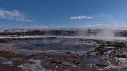 View of steaming water pool of famous geyser Strokkur (Icelandic