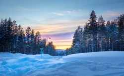 View of street with pine trees forest and mountain at sunset time with layer of colourful sky. At Kittila, Finland.