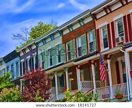 View of suburban street featuring colorful row houses.