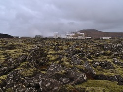 View of Svartsengi geothermal power station near Grindavik, Reykjanes peninsula, Iceland with moss covered lava field and rocky fissures in front on cloudy winter day.