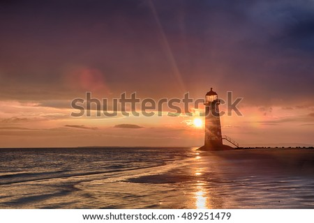 View of Talacre's lighthouse in Wales at sunrise near the sea. Blue sky and reflections on sand