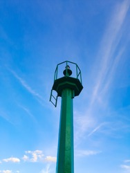 View of tall, green metal construction, point lighthouse against clear blue sky