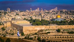 View of Temple Mount with Dome of the Rock and Al Aqsa Mosque, archaeological park of the Southern Wall and Huldah Gates, and skyline of new Jerusalem over the Old City; with Israeli flag in the front