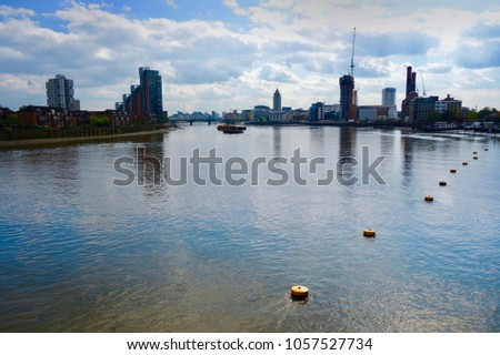 View of Thames river in London from bridge, West London cityscape on cloudy summer day                              #1057527734