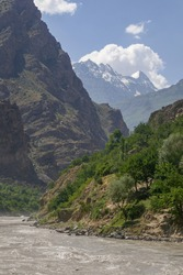 View of the Afghan side of the Panj river valley in Darvaz district in Gorno-Badakshan, the Pamir moutain region of Tajikistan, with snow-capped mountains in the background