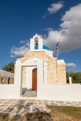View of the Agios Fokas, traditional orthodox Greek Church. Stone facade, belfry with a green bell. Paros Island, Greece, Aegean coast.