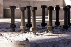 View of the anchor bolts for fondation in the concrete. An anchor bolt is a fastener used to attach objects or structures to concrete. There are many types of anchor bolts.
