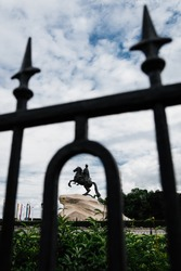 View of the ancient, 18th century, monument to Tsar Peter the Great in St. Petersburg through an old wrought-iron fence. Creative perspective