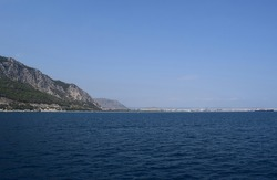 View of the Antalya from the Mediterranean sea - Antalya, Turkey. A view of the peaks of the Taurus Mountains and aquamarine sea water in popular touristic resort on Mediterranean sea in Turkey