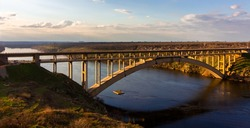 View of the arched bridge in the evening at sunset. Ukraine, the city of zaporizhia. Preobrazhensky Bridge across the Dnieper River. Beautiful landscape.