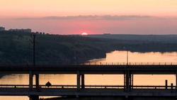 View of the arched bridge in the evening at sunset. Ukraine, the city of zaporizhia. Preobrazhensky Bridge across the Dnieper River.