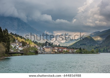 view of the Barcis city on the lakeside surrounding mountains against a dramatic cloudy blue sky background in Valcellina, Pordenone, Italy  #644856988