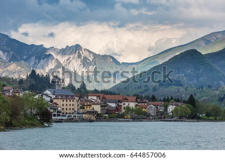 view of the Barcis city on the lakeside surrounding mountains against a dramatic cloudy blue sky background in Valcellina, Pordenone, Italy  #644857006