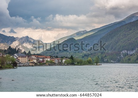 view of the Barcis city on the lakeside surrounding mountains against a dramatic cloudy blue sky background in Valcellina, Pordenone, Italy  #644857024